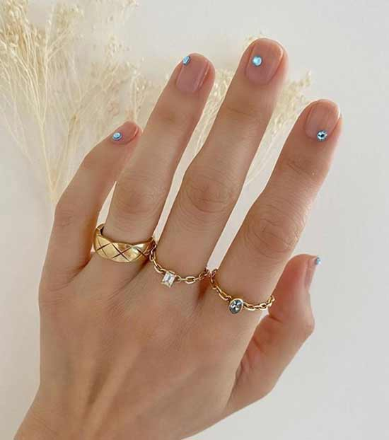 Голубые стразы на прозрачном фоне ногтей